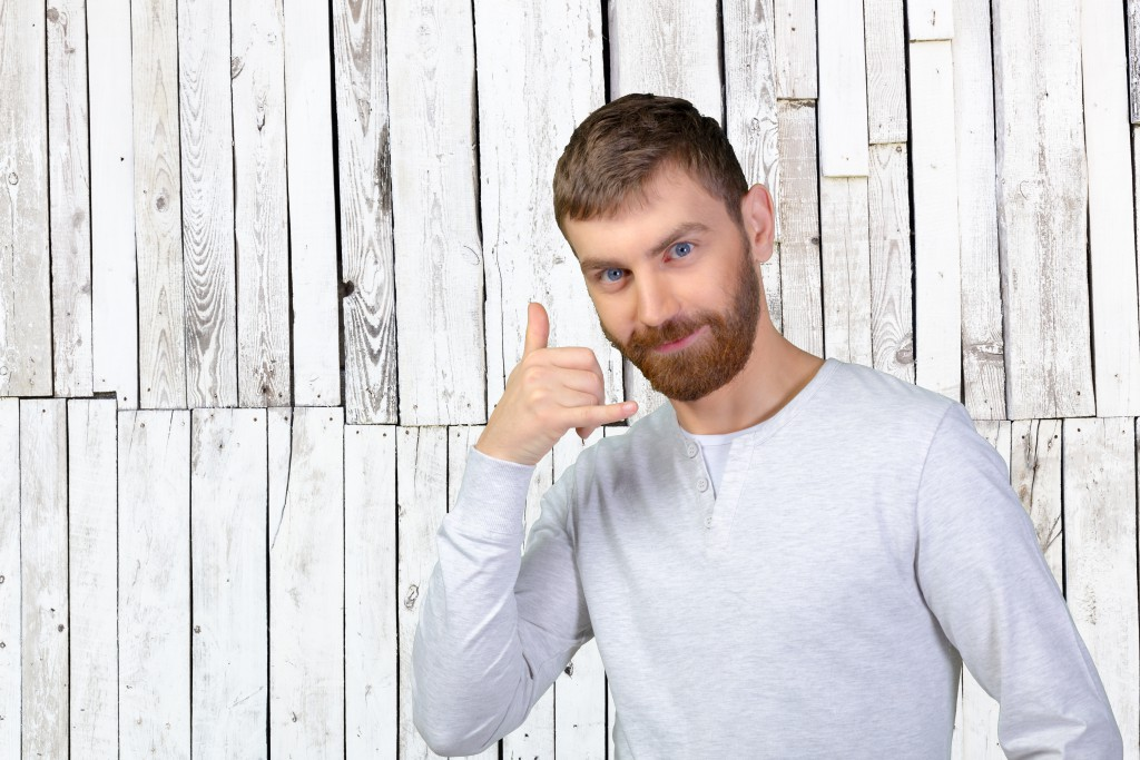 Young man using a call me gesture