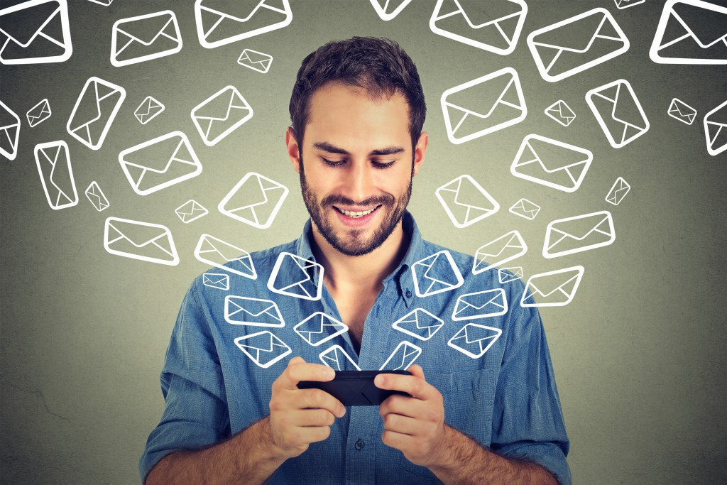 Portrait young happy man busy sending messages emails from smart phone