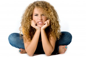 A happy teenage girl with curly hair on white background